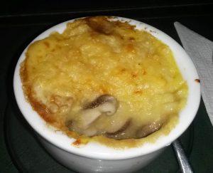 Mix de cogumelos: shitake, champignon holandês e shimeji, temperados com alho, azeite e shoyo, cobertos com polenta mole (feita com água) à moda italiana e gratinados com queijo parmesão vegano.